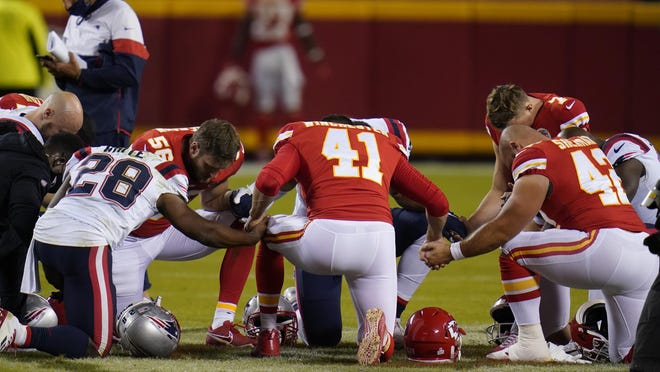 New England Patriots running back James White (28), Kansas City Chiefs linebacker Ben Niemann (56), James Winchester (41) and Kansas City Chiefs running back Anthony Sherman (42) hold hands to pray after an NFL football game, Monday, Oct. 5, 2020, in Kansas City. The Chiefs won 26-10.