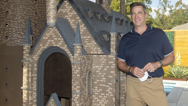 """Joel Pace poses next to his re-creation of Hogwarts Castle inside his Circle C backyard on Oct. 9. Each year since 2017, Pace has built a Halloween-timed """"Harry Potter""""-themed display."""