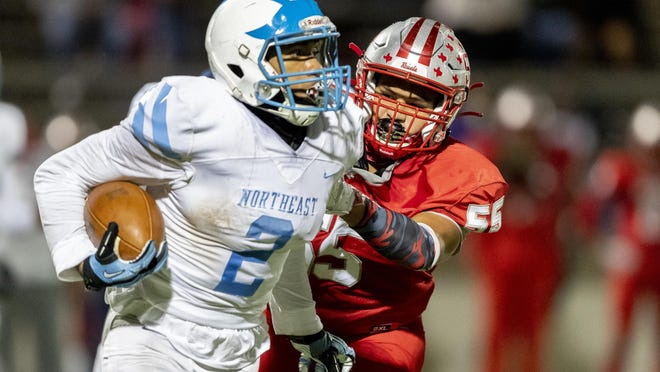 Northeast running back Da'Corey Eason, left, tries to escape the grasp of Travis defensive lineman Francisco Cazares during a District 14-5A Division II high school football game at House Park on Thursday. Eason had a 70-yard fumble return in overtime to lift Northeast to an 18-12 win over Travis.