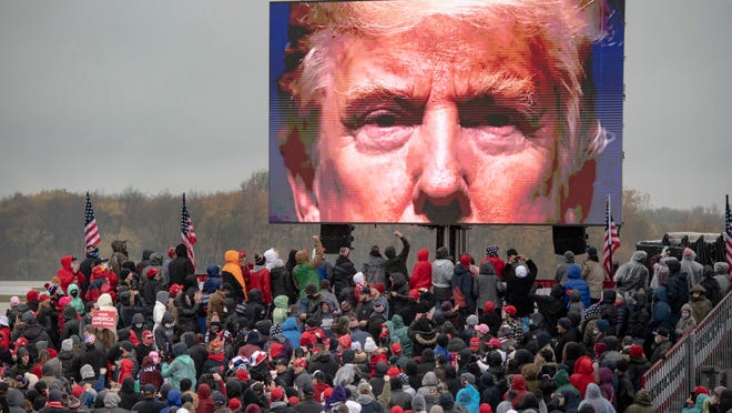 Supporters of President Donald Trump watch a video screen showing his face during a campaign event on Tuesday, Oct. 27, 2020, in Lansing, Mich.