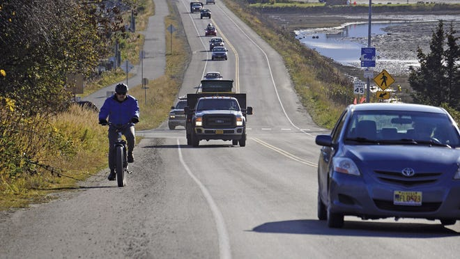 A biker leads a line of cars driving off the Homer Spit at about on Monday, Oct. 19, 2020, in Homer, Alaska after a tsunami evacuation order was issued for low-lying areas in Homer.