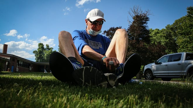 "Hopedale High running coach, Joe Drugan, 76, puts his shoes on in preparation to run the ""Crush Corona"" 5K starting at Hopedale Memorial Elementary School on Jun. 12, 2020."