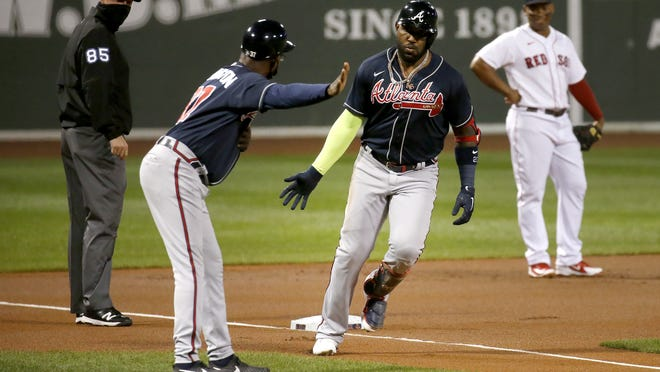 Atlanta Braves' Marcell Ozuna is congratulated by third base coach Ron Washington after hitting a two-run home run during the first inning of the team's baseball game against the Boston Red Sox, Tuesday, Sept. 1, 2020, in Boston.
