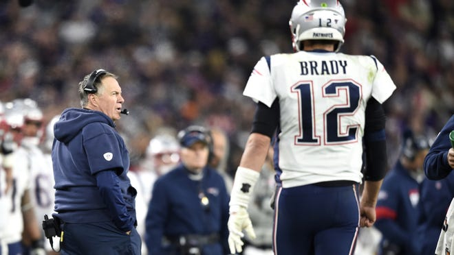New England Patriots head coach Bill Belichick (left) looks on as former quarterback Tom Brady heads to the bench after a series against the Baltimore Ravens on Nov. 3, 2019, in Baltimore. Despite Brady now playing for the Tampa Bay Buccaneers, Pats fans are still keeping tabs on how their former QB is stacking up against their current head coach in Belichick.