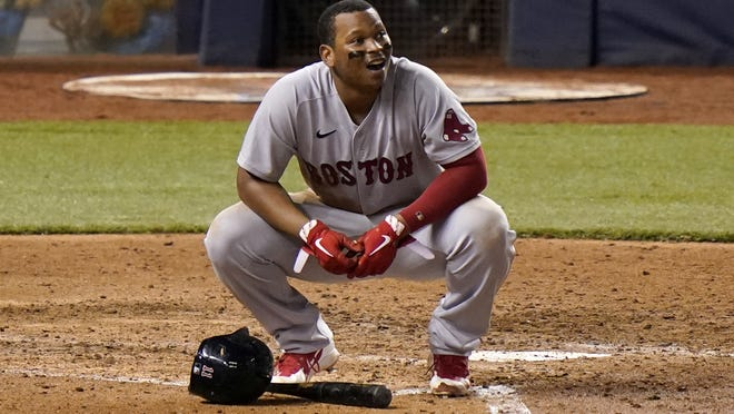 Boston Red Sox third baseman Rafael Devers kneels at the plate after striking out with the bases loaded during the sixth inning of a baseball game against the Miami Marlins, Wednesday, Sept. 16, 2020, in Miami. The Marlins won 8-4.