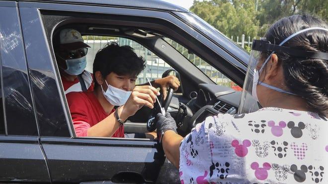 Jorge Angel Llamas, left, takes a COVID-19 test under the supervision of nurse Karen Barringer in Chula Vista on Sept. 4.