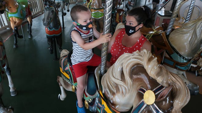 Logan Keenan, 4, and Abbi Keenan, both off Hull, take a ride on the Paragon Carousel, which reopened on June 29.