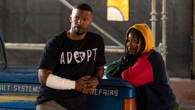 """This image released by Netflix shows Jamie Foxx, left, and Dominique Fishback in a scene from """"Project Power."""""""