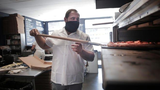 Donato Frattaroli, co-owner of Boardwalk Pizza, puts a pizza in the oven.