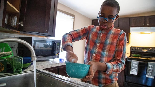 Isaiah Jolly, 10, washes the dishes at his familyís home on Friday, July 17, 2020. This fall he and his younger brother will not attend in person school to help protect them from the coronavirus.