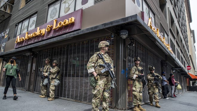 National Guard troops stand guard at the corner of Seventh Street and Broadway, in the heart of the jewelry district, as George Floyd protests continue in downtown Los Angeles.