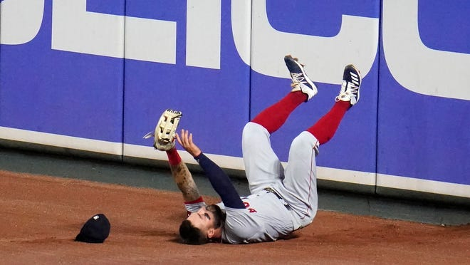 Boston Red Sox right fielder Kevin Pillar falls back onto the warning track after hitting the wall while making a catch on a ball hit by Baltimore Orioles' Ryan Mountcastle during the fifth inning of a baseball game, Saturday, Aug. 22, 2020, in Baltimore.