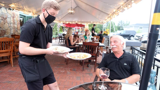 Jacques Ouimet, right, enjoys a meal and conversation with his server, Dennis Reilly, at Trattoria San Pietro in Norwell