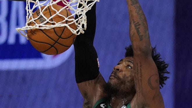 Boston Celtics guard Marcus Smart dunks the ball during the first half of an NBA conference semifinal playoff basketball game against the Toronto Raptors on Monday in Lake Buena Vista, Fla.