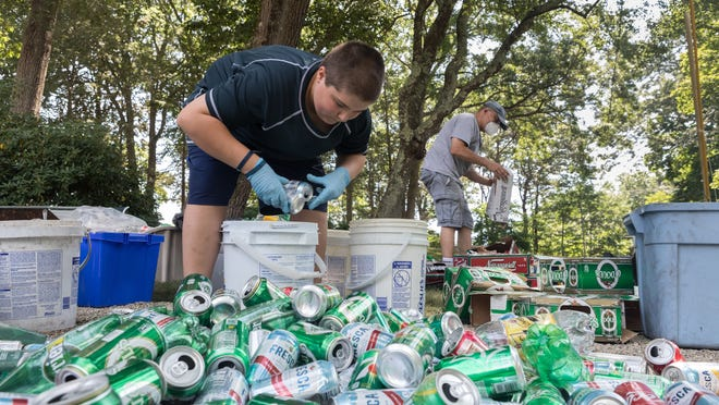 Michael Faucher, left 13 years old from Haverhill and his father John Faucher, right, help sort out the recycling at his grandparents' home to raise funds for ALS research on Saturday July 25, 2020. Photo by Lauren Owens Lambert / for The Patriot Ledger.