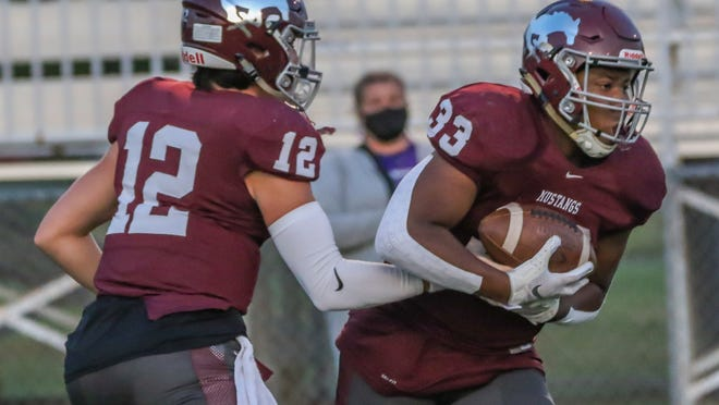 Salina Central's Parker Kavanagh (12)  hands the football off to running back Micah Moore (33) against Valley Center in 2020.