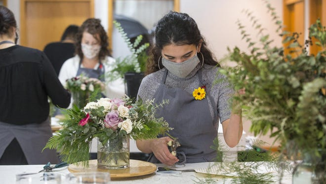 Floral arranger Nicole Zurita works during Friday's grand opening of Floracracy at the Talcott Building in Rockford.