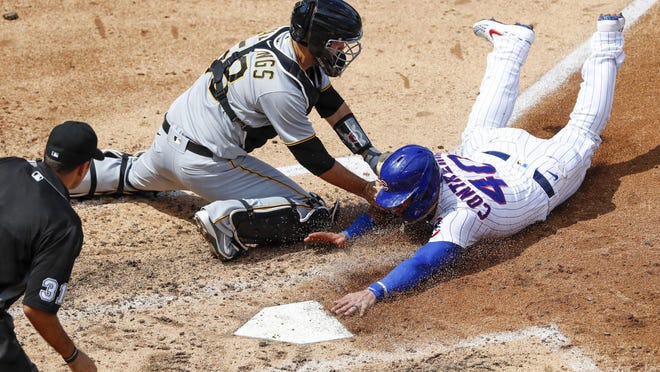 Chicago Cubs catcher Willson Contreras slides safely under the tag of Pittsburgh Pirates catcher Jacob Stallings in the fifth inning on Sunday at Wrigley Field in Chicago.