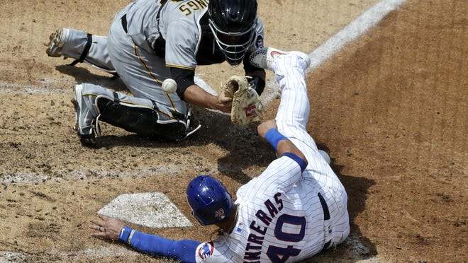 Chicago Cubs' Willson Contreras, bottom, scores on a one-run double by Kyle Schwarber as Pittsburgh Pirates catcher Jacob Stallings misses the catch during the fifth inning of a baseball game in Chicago on Sunday.