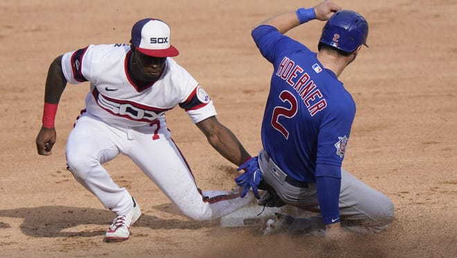 Chicago White Sox shortstop Tim Anderson, left, tags out Chicago Cubs' Nico Hoerner at second on Sunday. In the playoffs, the White Sox take on the Athletics and the Cubs face the Marlins.