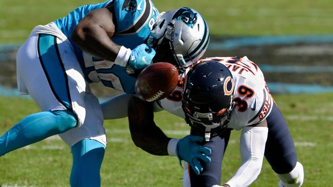 Eddie Jackson (39) of the Chicago Bears forces a fumble against Mike Davis (28) of the Carolina Panthers in the third quarter on Sunday at Bank of America Stadium in Charlotte, North Carolina.
