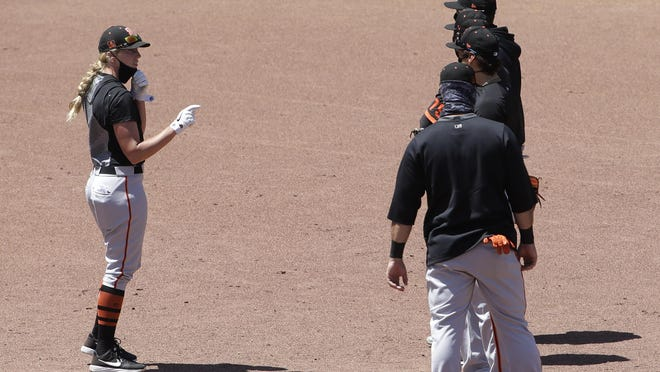 San Francisco Giants assistant coach Alyssa Nakken, left, talks with players during a baseball practice in San Francisco, Tuesday, July 14, 2020.