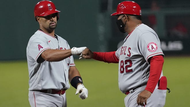 Los Angeles Angels' Albert Pujols, left, is congratulated by first base coach Jesus Feliciano after hitting a run-scoring single against the San Francisco Giants on Wednesday. The RBI tied the former Peoria Chiefs player with Alex Rodriguez for third on the all-time list.