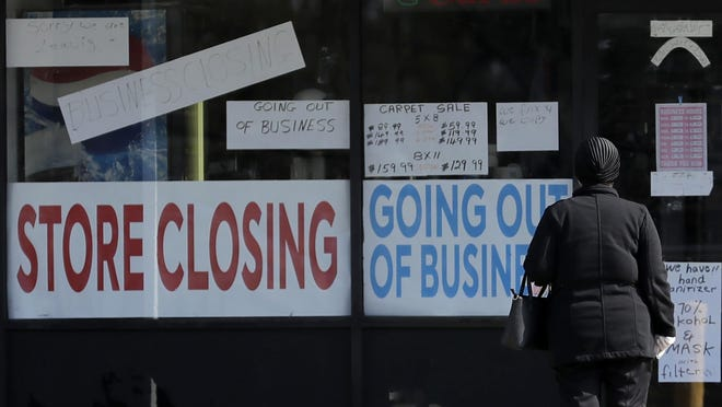A woman looks at signs at a store closed due to COVID-19 in Niles, Ill., Wednesday, May 13.