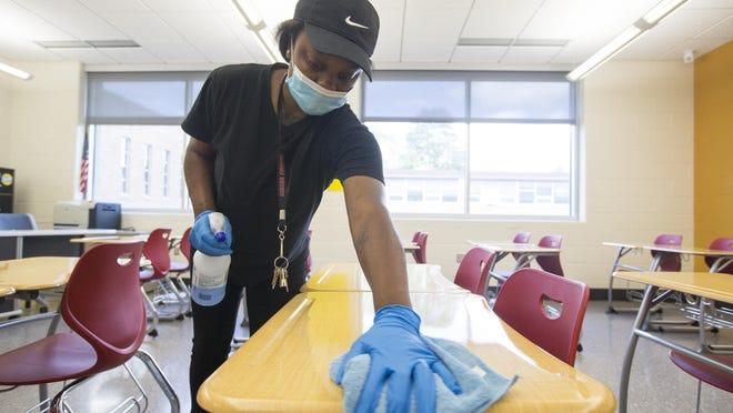 Cutlass Robinson, a second shift custodian, cleans and disinfects classroom desks at Auburn High School on Thursday, July 16, 2020, in Rockford.