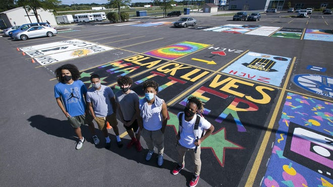 Rockford Christian students, from left, junior Isaac Johnson, senior Michael Hodges, senior Craig Cornelius, freshman Martez Taylor, and eighth-grader Elijah Daugherty pose for a photo on Wednesday where senior students painted designs onto their own parking spot as part of a fundraiser at Rockford Christian Schools.