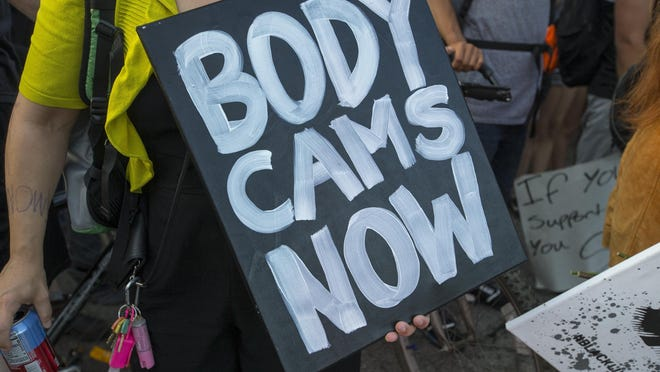 A protester holds a sign demanding body cameras for police officers on Saturday, June 6, 2020, during a march through Rockford. Action 4 Change, a group separate from the one that has led recent protests, shares a common goal of ending racism and police brutality. The grassroots group is circulating petitions demanding body cameras