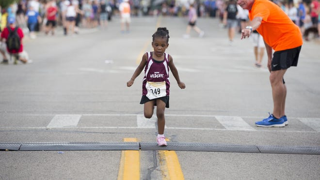 A young runner crosses the finish line of the State Street Mile on Aug. 3, 2019, at Water Street and State Street in Rockford. This year's race has been canceled due to the spread of COVID-19 caused by the coronavirus.