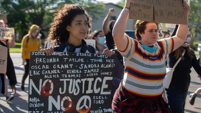Protesters walk along Pepper Drive on Sunday, June 14, 2020, in Rockford. Rockford Youth Activism leads a ninth night of marching at various locations.