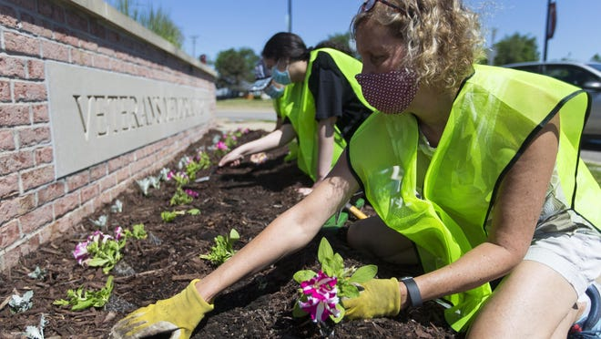 Sally Mark, from right, president of the Churchill's Grove Neighborhood Association, Fatima Khalil and Ayah Gheith plant flowers on Thursday, June 11, 2020, at Veterans Memorial Circle in Rockford.