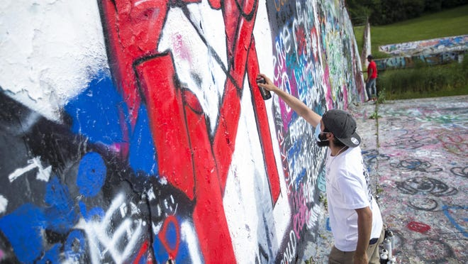 Multimedia creator Rodrigo Ceballos adds paint to his large mural during a Rockford Youth Activism cookout and mural painting event at Reuben Aldeen Lake Park on Saturday, June 27, 2020, in Rockford.