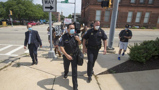 Demonstrators shouting anti-police slogans follow Police Chief Dan O'Shea to the emergency dispatch center Thursday in downtown Rockford. The Rockford Board of Fire and Police Commissioners unanimously found no probable cause to proceed to a full probe of bias allegations against O'Shea.