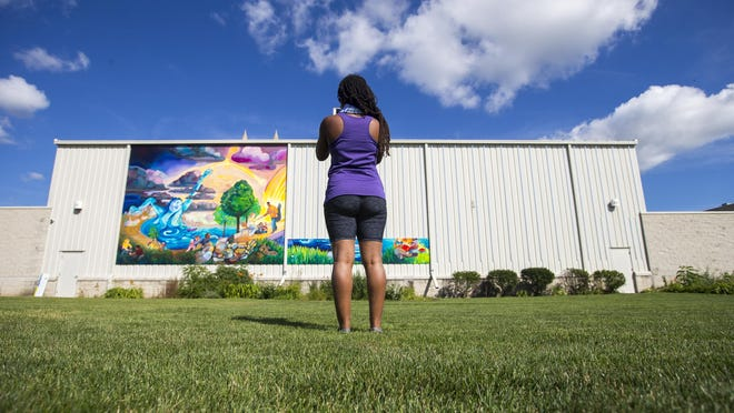 Muralist Tia Richardson photographs the results of the first day of panel installation at Second First Church on Thursday, July 16, 2020, in Rockford. Over 50 community members participated in image design and painting the city's newest mural to be fully installed after this weekend.