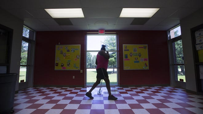Custodian Ronda Stone applies finish to the floor at RESA Middle School on Friday. Rockford Public Schools plans to reopen all of its schools this fall.