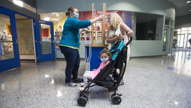 Guest Services Manager Hillary Parks, left, conducts a wellness check-in with Susan Sunday of Rockford, right, and Serafina Davila, in the stroller, before they enter the Discovery Center on Thursday in Rockford. Staff and visitors are taking health safety precautions while the museum limits public access.