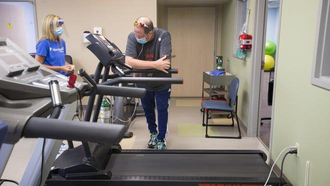Tim Rundblade, 46, of Rockford, with his physical therapist Kelly Hix, rests to catch his breath after physical therapy exercises at Mercyhealth Javon Bea Hospital-Rockton on Tuesday in Rockford. Rundblade was on a ventilator for 14 days after contracting COVID-19 in late March. He is still recovering.