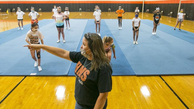 Susan Schaefer, a Harlem Middle School cheer coach, instructs students to remain six feet apart on Wednesday, the first day of tryouts at Harlem High School in Machesney Park.