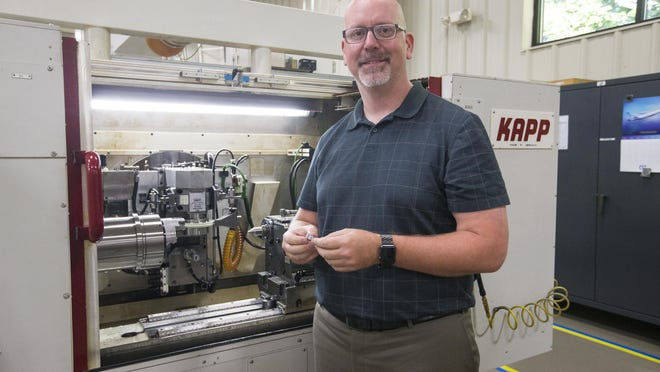 Jared Lyford, director of manufacturing operations of Forest City Gear Company, shows a gear and its cutting machine on Friday in Roscoe. The company made gears for NASA's Perseverance rover that launched to Mars on Thursday.