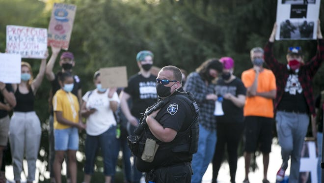 A Metro Enforcement security officer watches protesters on July 24 at Rockford City Market. City Market organizers said Thursday that this week's event would be canceled because of the ongoing demonstrations.