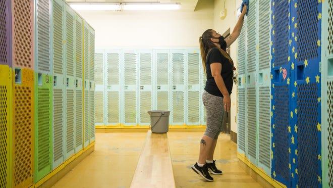 Custodian Rebecca Greiner cleans the outside of lockers in the girls locker room at Jefferson High School in Rockford.