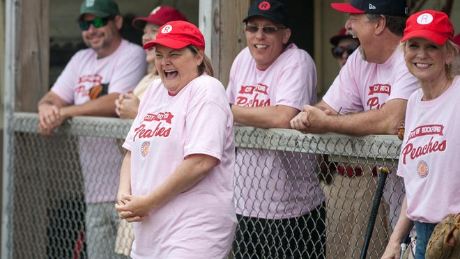 """Megan Cavanagh, center, who portrayed Rockford Peaches player Marla Hooch in the movie, """"A League of Their Own,"""" laughs from the sidelines during an exhibition game on June 2, 2018, at Beyer Stadium in Rockford. Cavanaugh and other stars attended a """"Play Ball for Penny"""" VIP reception Friday at Indoor City Market as part of the weekend-long Penny Marshall Celebration."""