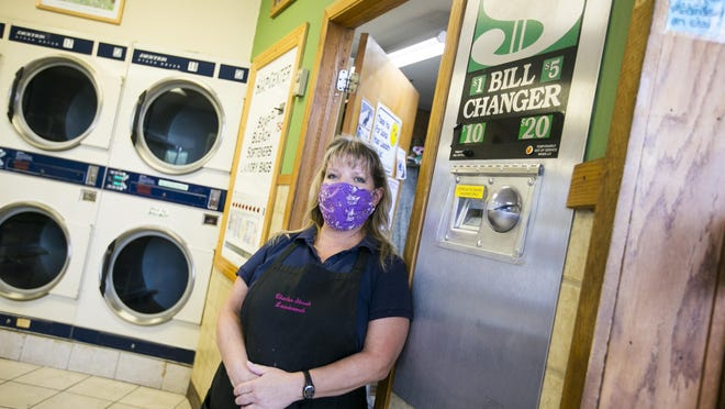 """Suzanne Forthenberry, an attendant at Charles Street Laundromat, next to a coin changer with a sign that reads: """"Coins are for laundry customers only."""""""