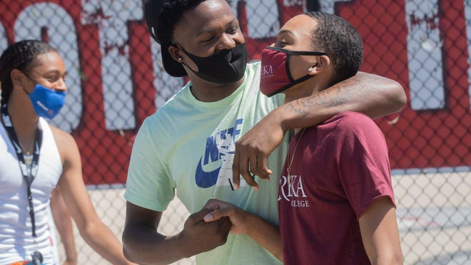 Javente Mackey congratulates Haniefe Johnson after signing his commitment with Eureka College at Auburn High School on Wednesday in Rockford.