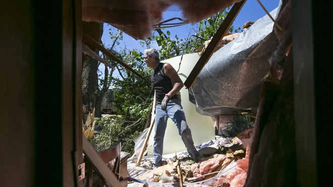 Dan Rippy of Forreston clears debris Tuesday from his granddaughter's bedroom in a home in the Candlelight Mobile Home Park in Forreston.