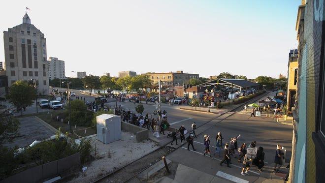 Demonstrators march outside Rockford City Market on Aug. 21 in Rockford.