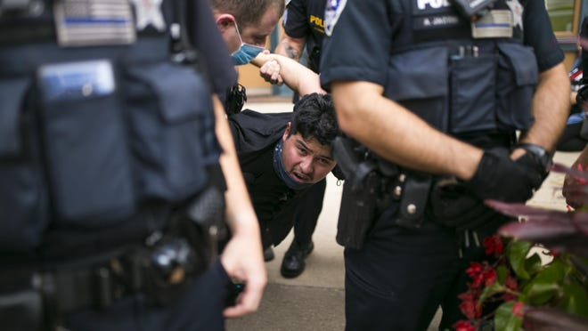 Rockford police arrest a demonstrator outside of Runner's Image on Friday in downtown Rockford.